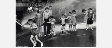 Fotografía en blanco y negro con niños mojándose con una manguera