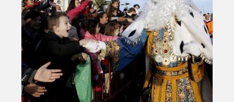 Foto del Rey Melchor dando la mano a un niño durante la cablagata